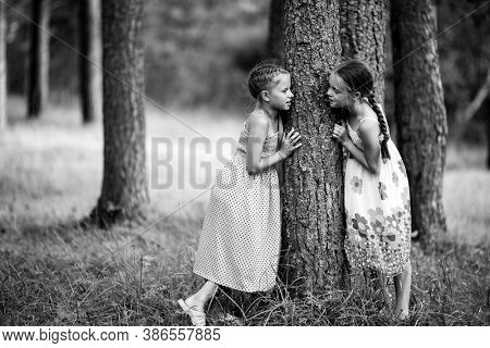 Two little girl friends in the park. Black and white photo.