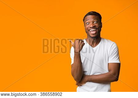 Look There. Excited Afro Man Pointing Thumbs At Copy Space Looking At Camera Standing Over Orange Ba