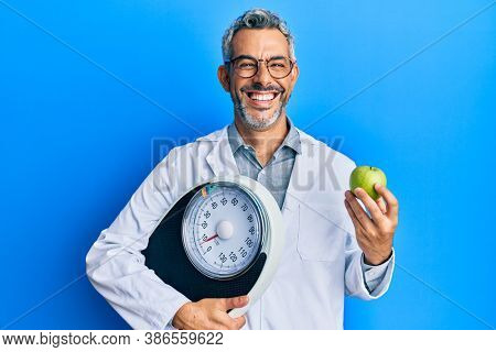 Middle age grey-haired man as nutritionist doctor holding weighing machine and green apple smiling and laughing hard out loud because funny crazy joke.