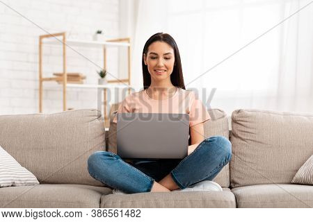 Lifestyle Concept. Happy Smiling Woman Using Laptop Sitting On Sofa In Living Room At Home, Watching
