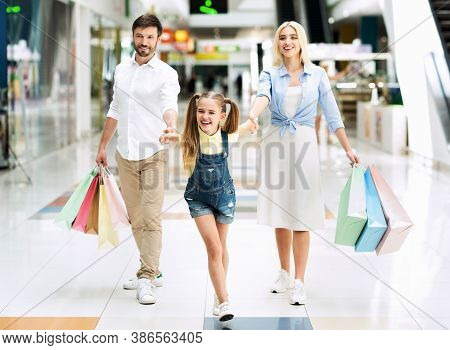 Sales Season. Family Of Three Carrying Shopper Bags After Successful Shopping In Mall.