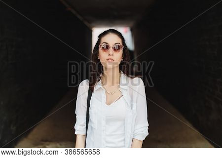 Woman In Sunglasses In A Dark Hallway.