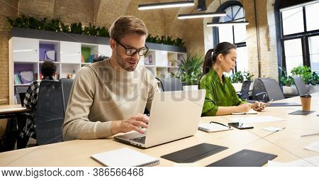 Young Focused Caucasian Man Wearing Eyeglasses Working On Laptop While Sitting At Desk With His Fema