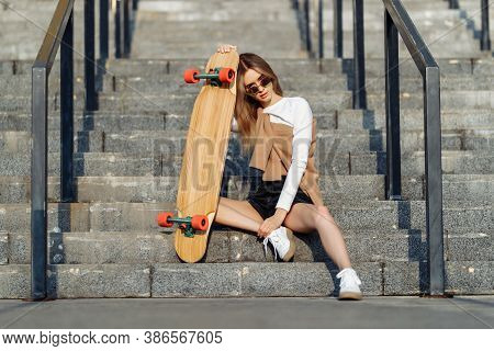 Sexy Blonde With A Longboard Sits On The Stairs In Short Shorts.