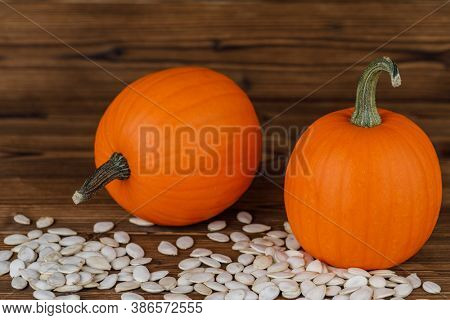 Two Pumpkins and many seeds on wooden background
