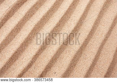 Dry Sand Surface With Grooves And Wavy Lines Close-up Diagonal Top View With Shallow Depth Of Field