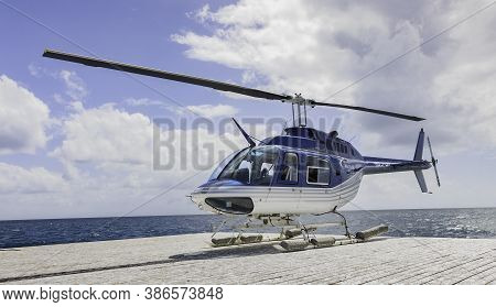 The Great Barrier Reef, Australia - March 17th, 2020: A tourist helicopter on a floating wharf at the great barrier reef, on a cloudy day.