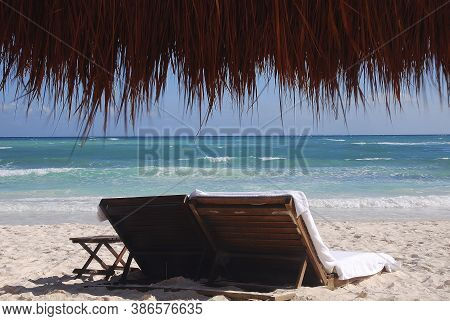 Empty beach loungers on a deserted tropical beach with natural straw and wood umbrella, Cancun, Mexico