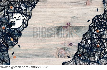 Halloween background. Spider web, cobweb lace and spooky ghost Halloween decorations, symbols of Halloween on the wooden background. Halloween card, festive Halloween background