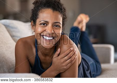 Portrait of young african woman lying on couch and looking at camera. Beautiful and happy young woman lying on front while relaxing at home. Carefree black smiling lady relaxing on sofa.