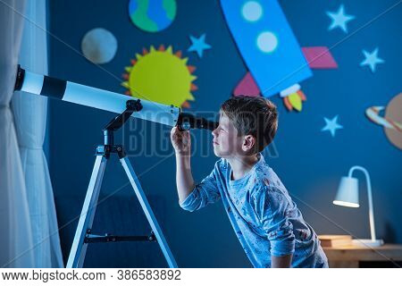 Curious boy using telescope to explore moon surface at night in his bedroom. Young child using telescope to see remote galaxy from room with decorated wall with rocket, planets, stars and spaceship.