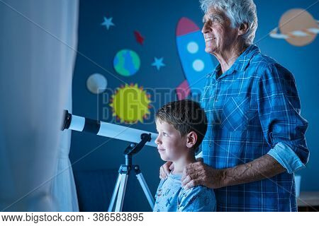 Smiling old man and little boy standing near window to watch the galaxy. Cheerful grandfather and happy grandson watching stars during night. Child and grandpa looking at their bright future concept.