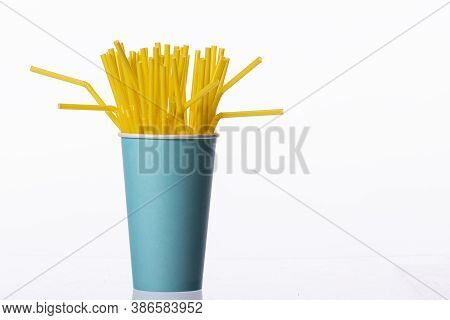 Yellow Plastic Flexible Straws In Blue Disposable Paper Cup Isolated On White Background. Cafe Drink