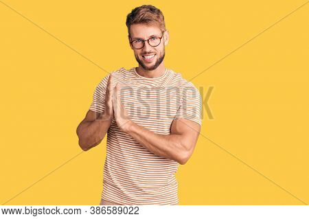 Young caucasian man wearing casual clothes and glasses clapping and applauding happy and joyful, smiling proud hands together