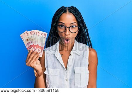 Beautiful hispanic woman holding 10 colombian pesos banknotes scared and amazed with open mouth for surprise, disbelief face