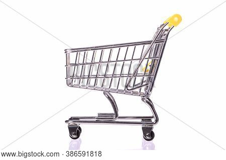 Shopping Concept. Empty Toy Shopping Trolley Isolated On White Background Side View. Idea For Discou