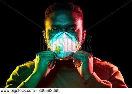 health, safety and pandemic concept - young african american man wearing protective mask or respirator over black background