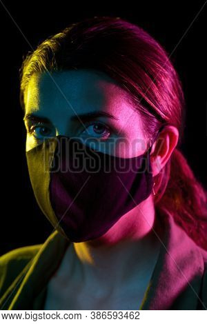 health, safety and pandemic concept - young woman wearing reusable protective mask over black background