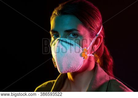 health, safety and pandemic concept - young woman wearing protective mask or respirator over black background