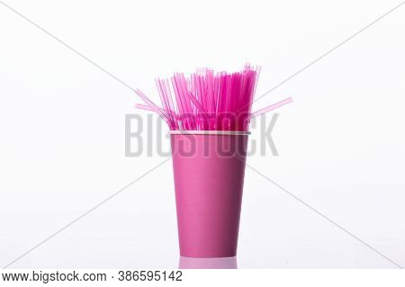 Bunch Of Pink Plastic Straws In Pink Disposable Biodegradable Paper Cup Isolated On White Background