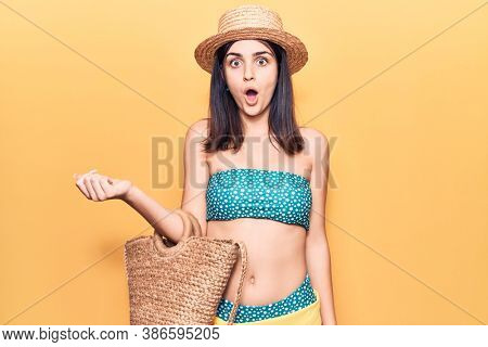 Young beautiful girl wearing bikini and hat holding bag scared and amazed with open mouth for surprise, disbelief face
