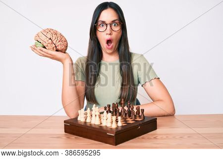 Young caucasian woman sitting at the desk playing chess holding brain scared and amazed with open mouth for surprise, disbelief face