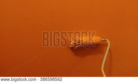 A Paint Roller Against The Orange Wall