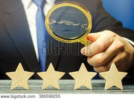 A Man Holds A Magnifying Glass Over Four Stars. The Evaluation Of Visitors. Quality Level, Good Serv