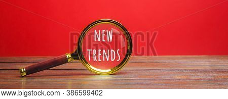 Magnifying Glass With The Inscription New Trends. The Concept Of Searching For New Ideological Trend