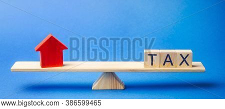 Wooden Blocks With The Word Tax And A House On Scales. The Concept Of Paying Taxes On Real Estate An
