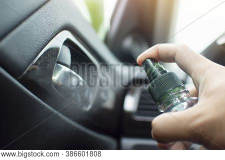 Cleaning Car Door Handle Inside With Alcohol Sanitizing Spray In A Car For Protection Disease And An