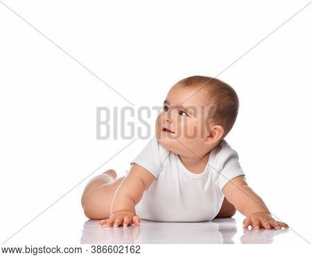 Smiling Baby Kid Creeping Or Crawling On White Studio Floor. Inquisitive Child Wearing Jumpsuit Look