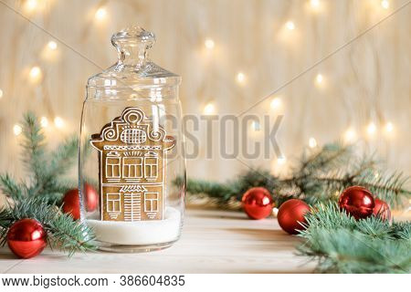 Christmas Gingerbread House In Glass Jar With Christmas Decorations And Defocused Golden Lights In B