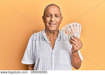 Handsome mature man holding 10 united kingdom pounds banknotes looking positive and happy standing and smiling with a confident smile showing teeth