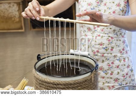 The Process Of Making Candles From Natural Wax . A Woman Holding Ropes Wicks Over Hot Wax