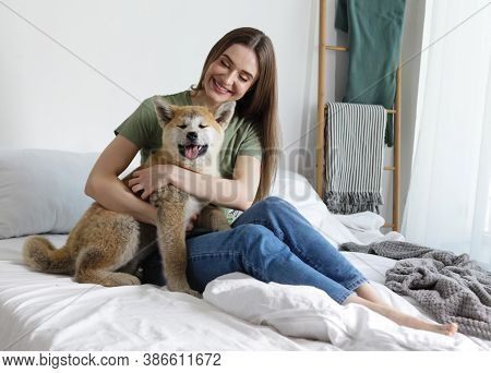 Happy Woman With Her Cute Akita Inu Puppy At Home