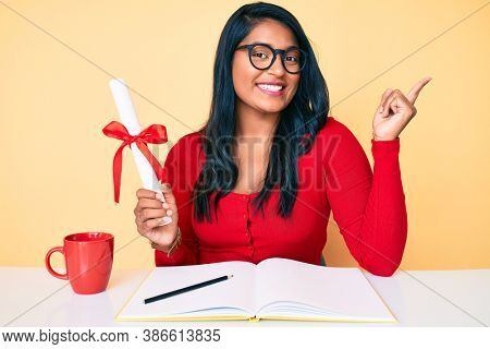 Beautiful latin young woman with long hair holding graduate degree diploma smiling happy pointing with hand and finger to the side