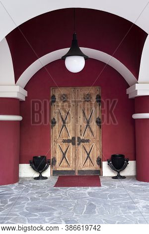 Antique Wooden Door On A Red Wall With White Arches