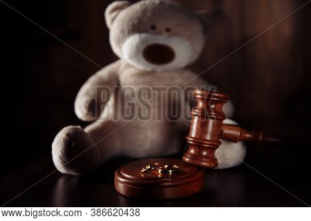 Divorce And Alimony Concept. Wooden Gavel, Rings And Teddy Bear As Symbol Of Child. Family Law