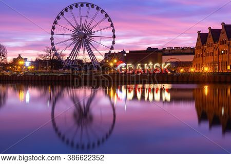 Motlawa River And Ferris Wheel With Water Reflection In Old Town Of Gdansk At Night, Poland
