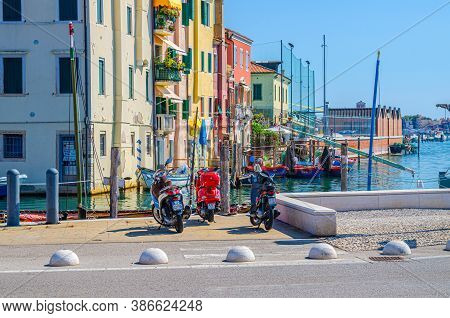 Chioggia, Italy, September 16, 2019: Motorcycles And Bikes Vespa On Embankment, Old Buildings And Bo
