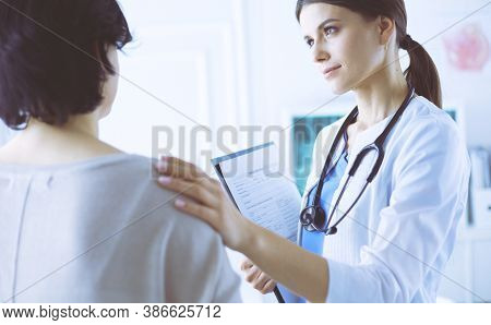 Medical Consultation. Female Doctor Holding A Patient By Her Shoulder, Soothing Her Fear