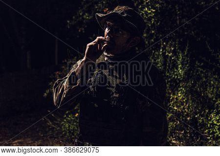Commando Soldier In Camouflage Uniform, Ballistic Glasses And Bonnie, Inhale Cigarette Smoke, Smokin