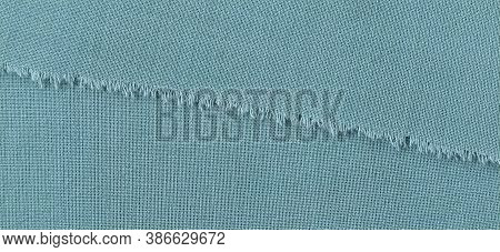Ripped Edge Of Fine Woolen Fabric In Green Or Blue. Loose Threads At The Edge Of A Piece Of Textile.