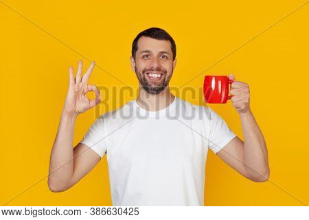 Young Man With A Beard In A White T-shirt Smiling, Holding A Red Cup Of Coffee And Showing The Gestu