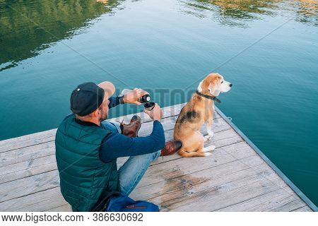 Man As A Dog Owner And His Friend Beagle Dog Are Sitting On The Wooden Pier On The Mountain Lake And