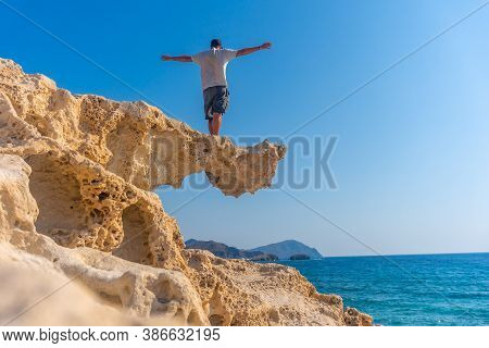 A Young Man Perched On The Rocks Looking At Playa Los Escullos In The Natural Park Of Cabo De Gata,
