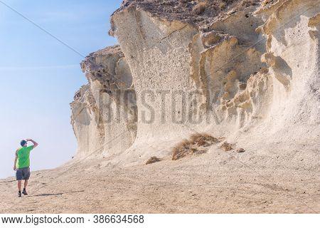 A Young Tourist Visiting The Gigantic White Rock Walls At Cala De Enmedio In The Cabo De Gata Natura