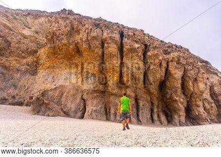A Young Man Visiting The Beautiful Natural Walls Of Playa De Los Muertos In The Natural Park Of Cabo