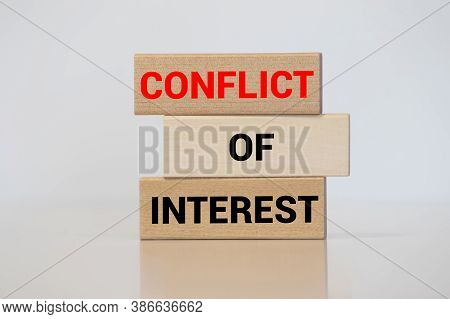 Male Hand Placing A Block With Word Conflict On Top Of A Blocks Tower With Words Conflict Of Interes